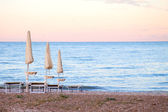Closed umbrellas on evening beach — Stock Photo