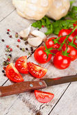 Fresh tomatoes, buns, spices and old knife — Stock Photo