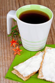Cup of tea and crackers with cream — Stock Photo