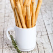 Cup with bread sticks grissini and rosemary — Stock Photo