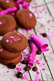 Chocolate cookies, coffee beans, pink ribbons and confetti — Stock Photo