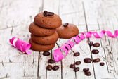 Fresh chocolate cookies, coffee beans and pink ribbons — Stock Photo