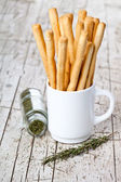 Cup with bread sticks grissini and rosemary — Stockfoto