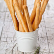 White bucket with bread sticks grissini and rosemary — Stock Photo