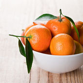 Tangerines with leaves in bowl — Stock Photo