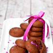 Plate of fresh chocolate cookies with pink ribbon and confetti — Stock Photo