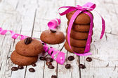 Stack of chocolate cookies tied with pink ribbon and coffee bean — Stock Photo