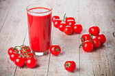 Tomato juice in glass and fresh tomatoes — Stock Photo