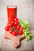 Tomato juice in glass, fresh tomatoes and green celery  — Zdjęcie stockowe