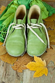Pair of green leather boots, scarf and yellow leaves — Stock Photo