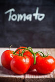 Fresh tomatoes and blackboard — Stock Photo