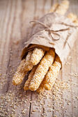 Bread sticks grissini with sesame seeds in craft pack — Stock Photo