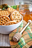 Fresh cookies in a bowl, tablecloth and honey — Stock Photo