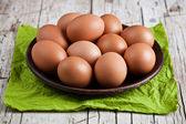 fresh brown eggs in plate and green napkin — Stock Photo