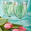 Two glasses of white wine and tulips — Stock Photo