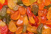 Bright fruit candy of the different form, motley background — Stock Photo