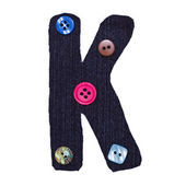 Letter K from fabric and button on the white — Stock Photo