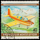 MONGOLIA - CIRCA 1980: A stamp printed in the MONGOLIA, shows plane against mountains, circa 1980 — Stockfoto
