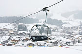 Ski lift chairs against of Kirhberg, Austria. Snowfall — Stock Photo