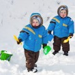 Stock Photo: One-year-old twins play in snow together