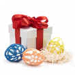 Foto Stock: Easter eggs and gift in a box with a bow