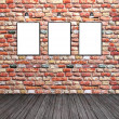 Three empty white frames on a brick wall — Stock Photo