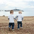 Twins go by a hand on a beach — Stockfoto
