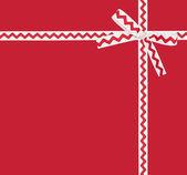 Cartão com fita branca com um ornamento vermelho — Fotografia Stock