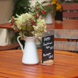 Flowers in pitcher on table. - Stock Photo