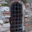 Door grille in an old brick wall. - Stock Photo