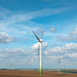 Wind power generators on the field. - Stock Photo
