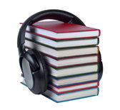 Headphones worn on a stack of books with color covers. — Stock Photo