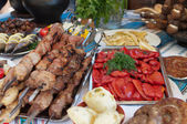 Meat and fish dishes with vegetables on the table. — Stock Photo