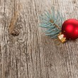 Royalty-Free Stock Photo: Red Christmas ball on wooden background with fir branch