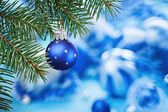 Christmas ball on blue spruce branch over blurred blue backgroun — Stock Photo