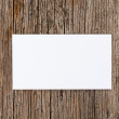 Empty white card over old textured wooden background — Stock Photo