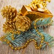 Christmas golden decorations on pine branch on wooden background — Stock Photo