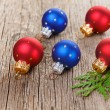 Christmas balls on wooden background with green thuja branch - Foto Stock