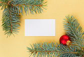 Empty card on golden Christmas background with spruce branches — Stock Photo