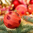 Red decoration ball with spruce branch on blurred  Christmas bac - Stockfoto