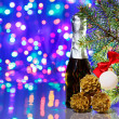 Christmas tree decorations with spruce and champagne on bokeh ba — Stock Photo