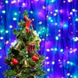 Decorated Christmas tree on multicolor bokeh background — Stock Photo