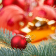 Red decoration ball with spruce branch macro - Stock Photo