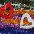 Christmas tinsel multicolored decoration with two hearts — Stock Photo