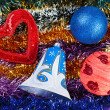 Christmas multicolored tinsel with decoration toys on it - Stock Photo