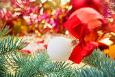 New Year ball with red bow on blurred decoration background — Stock Photo