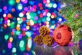 Czerwoną piłkę ozdoby świąteczne świerk i stożki na bokeh ba — Zdjęcie stockowe