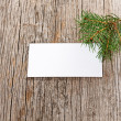 Wooden background with empty white card and fir branch - Stock Photo