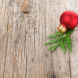 Stock Photo: Red Christmas ball on wooden background with green thuja branch