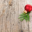 Red Christmas ball on wooden background with green thuja branch — Stock Photo